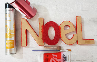 coller des paillettes rouge sur le mot noël en bois