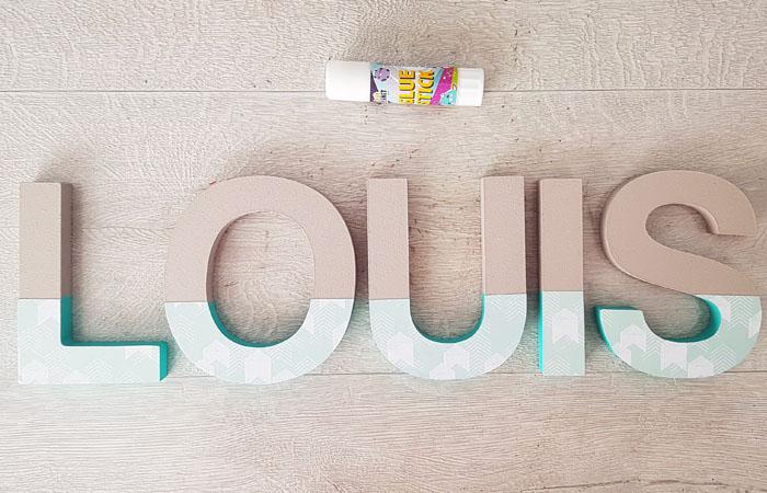 collage du papier bleu pastel flèches sur les lettres en bois à poser