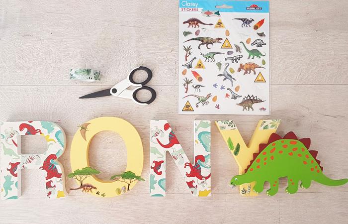 un tuto dinosaure en bois avec es lettres à poser
