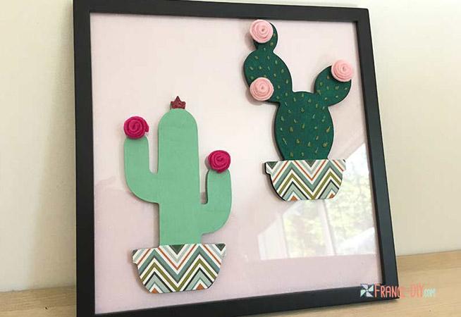 un cadre décoratif avec des cactus en bois