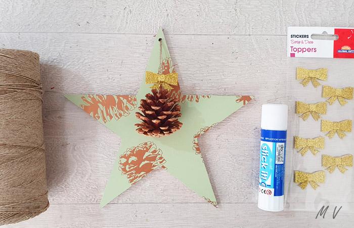 décoration d'étoile en bois avec du papier et une pomme de pin