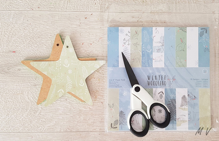coller du papier noël sur l'étoile en bois
